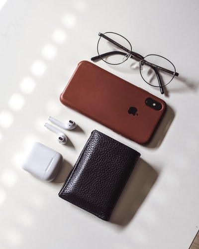 red iphone case beside white apple airpods