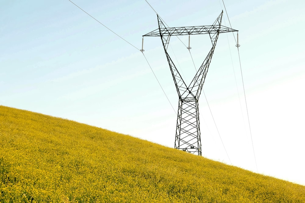 black metal electric tower on yellow grass field under white sky during daytime