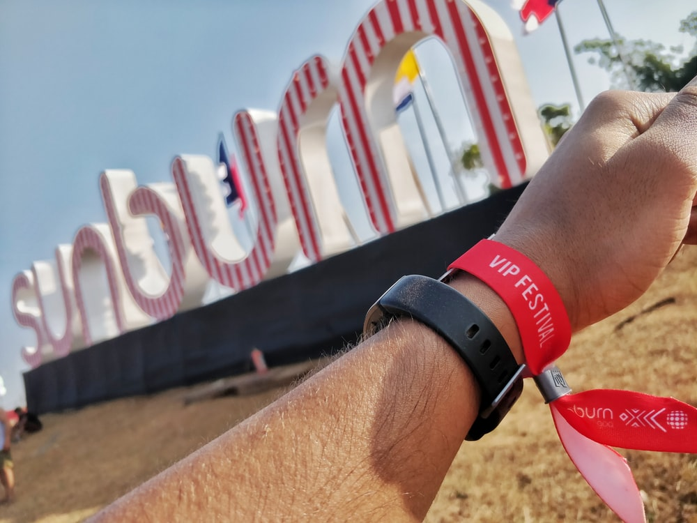 person wearing black and red silicone bands