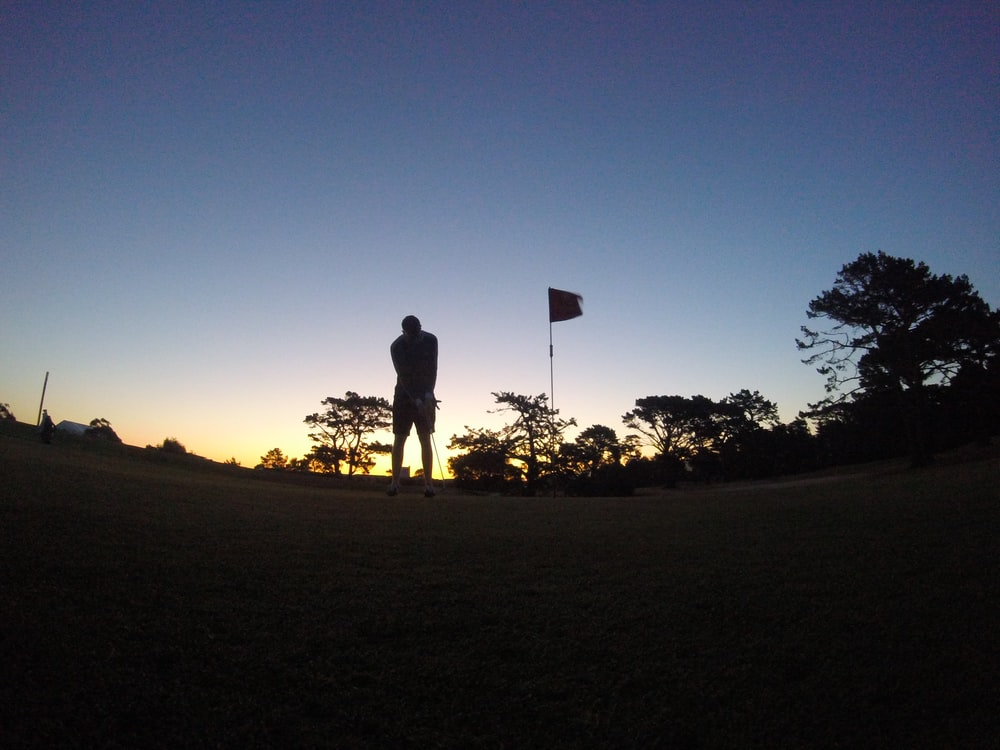 silhouette of man and woman standing on grass field during sunset