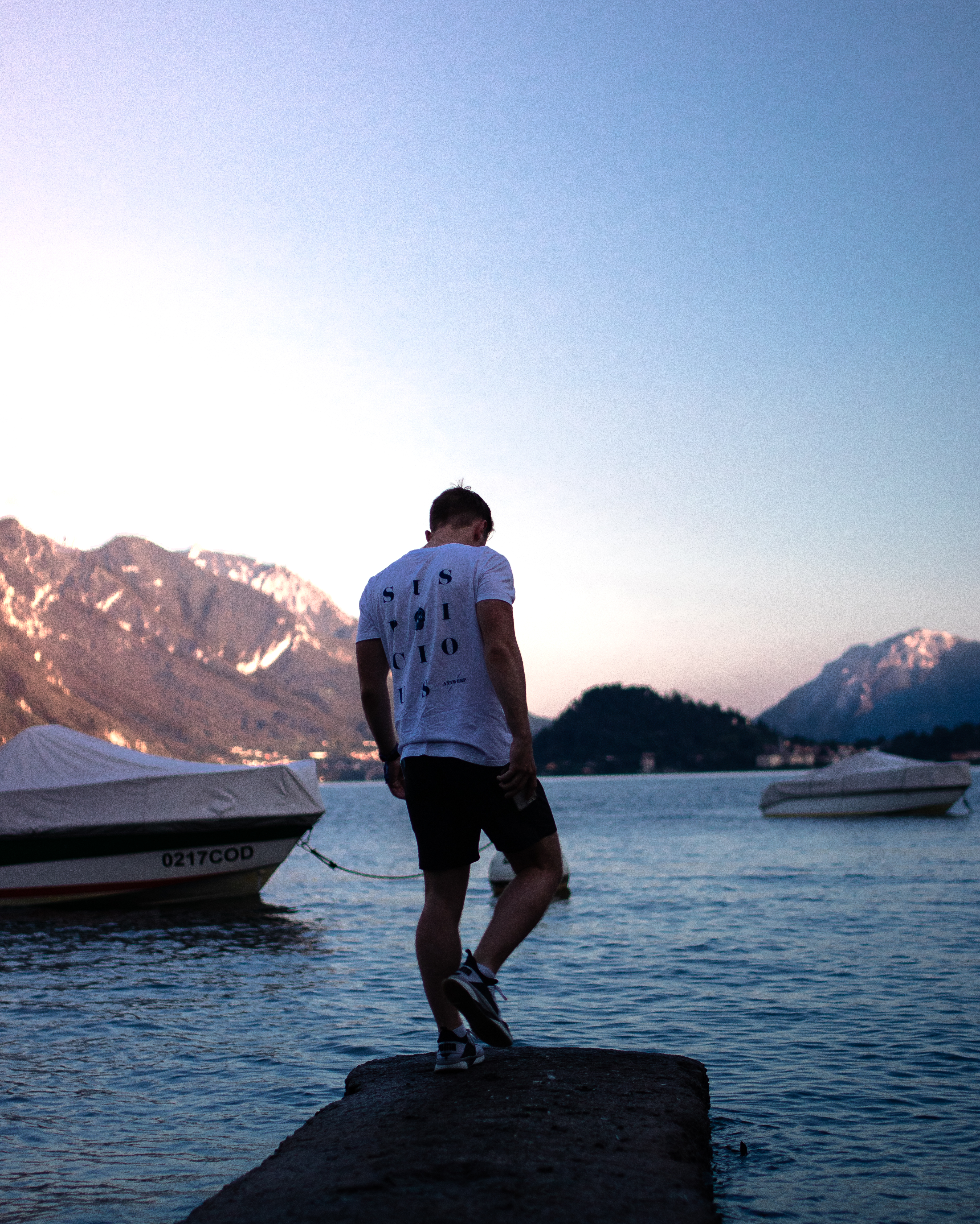 Man standing towards the lake with background of mountains water and boats