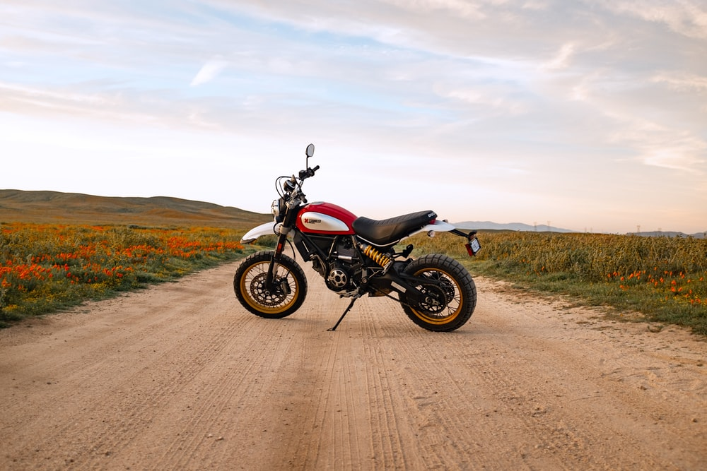 black and gray motorcycle on brown dirt road under white clouds during daytime