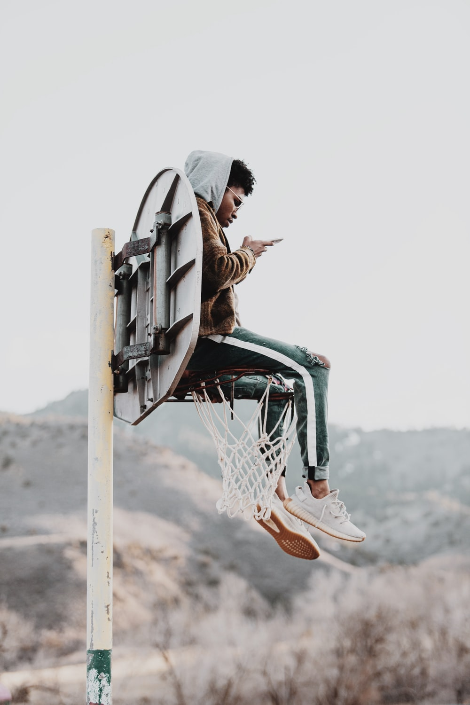 woman in brown jacket sitting on basketball hoop during daytime