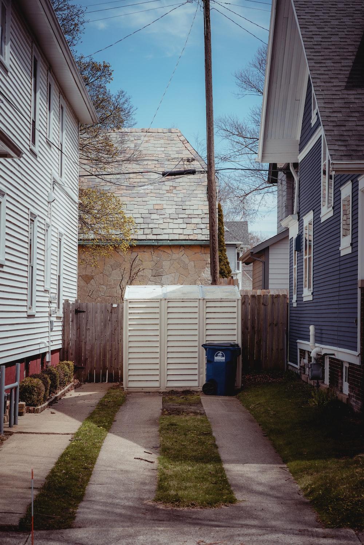 blue plastic trash bin beside brown brick wall