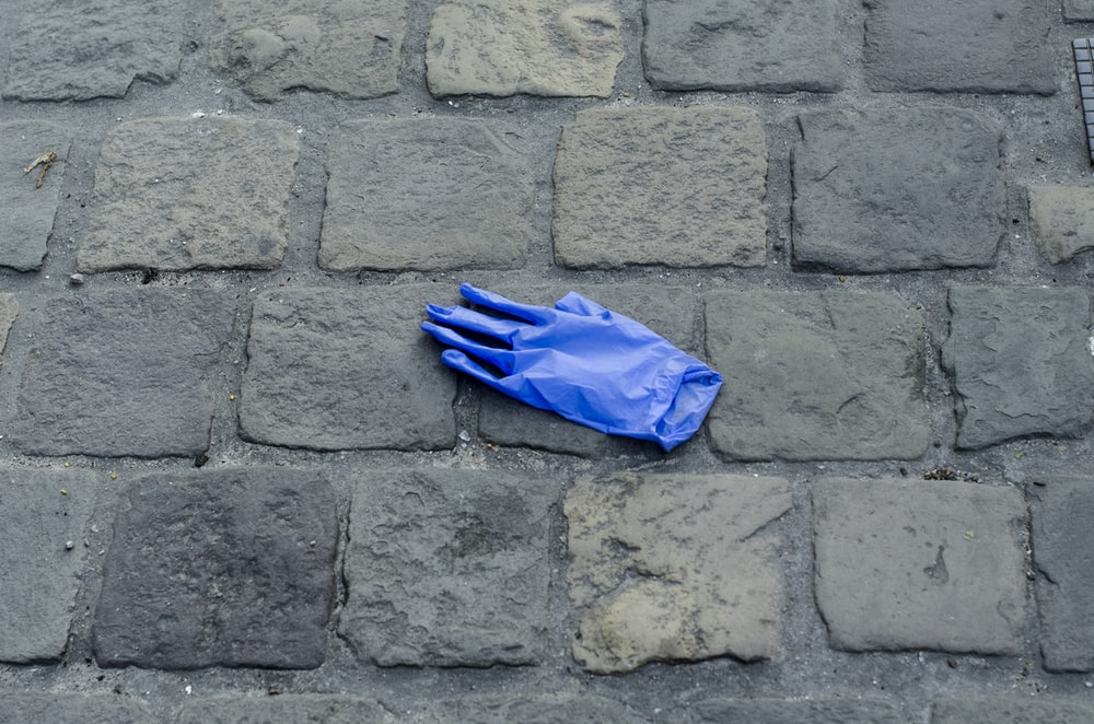 blue umbrella on gray brick floor