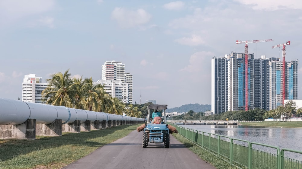 blue and black tractor on gray concrete road near city buildings during daytime