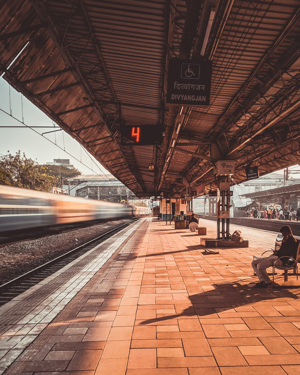 people sitting on bench near train rail during daytime