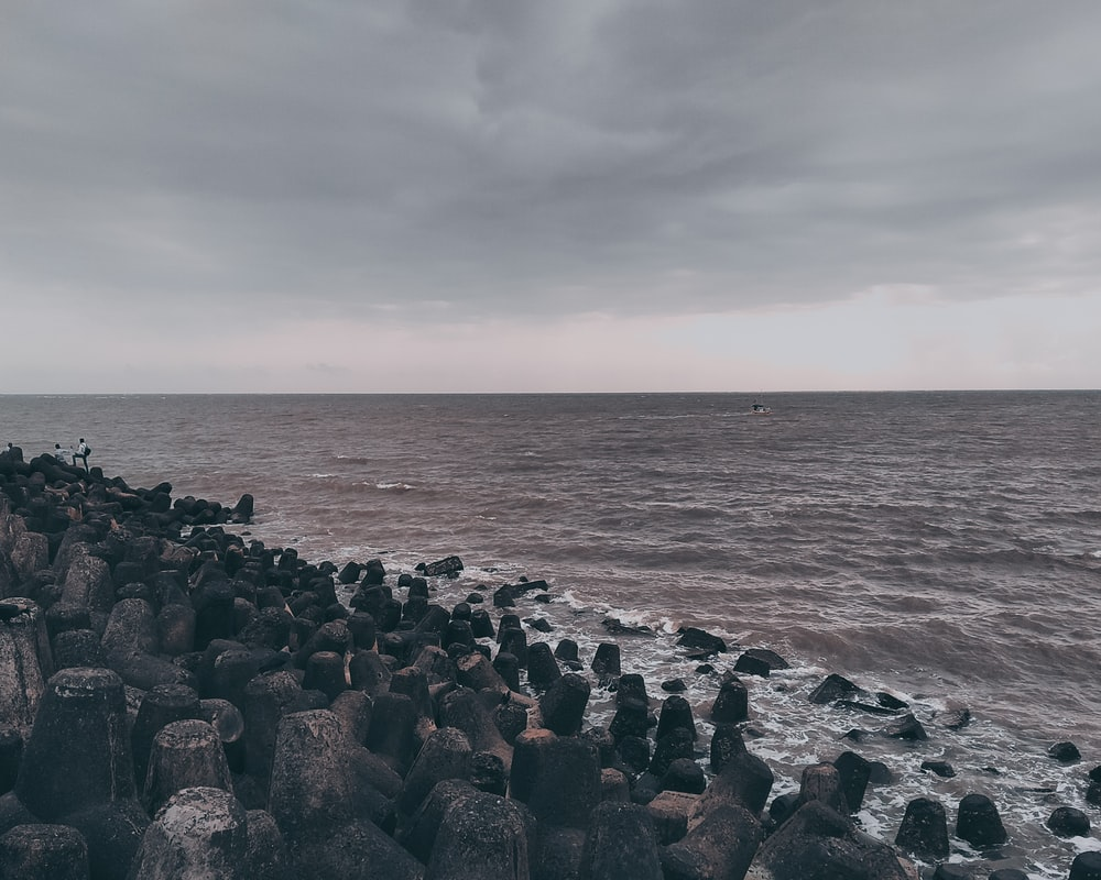 gray and black rocks near body of water under cloudy sky during daytime