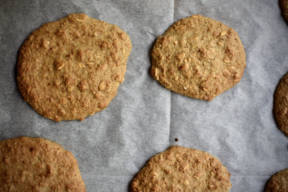 two brown cookies on white textile