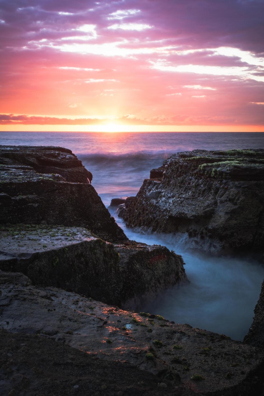 rocky mountain near sea during sunset