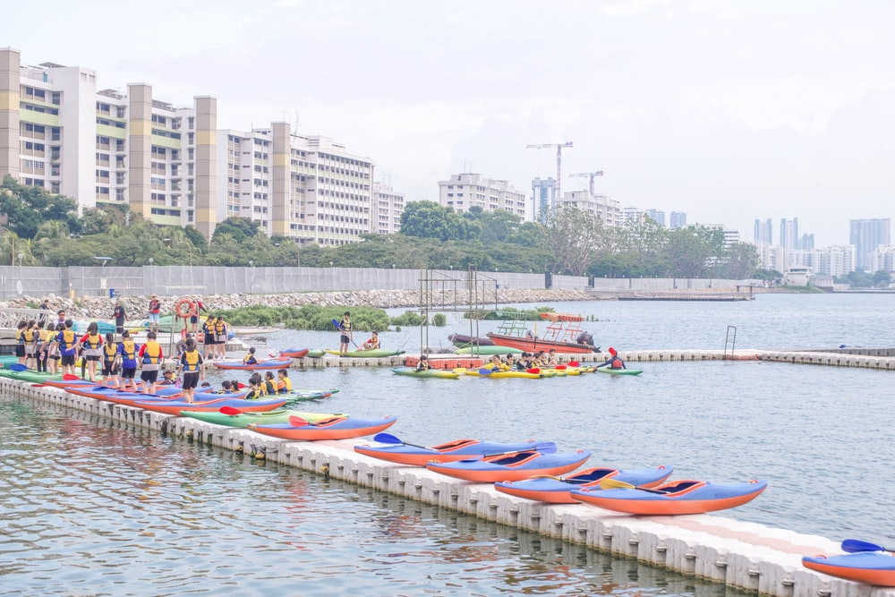 people riding on kayaks on body of water during daytime