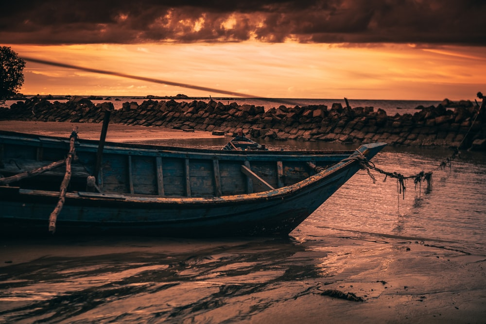 brown boat on sea shore during sunset