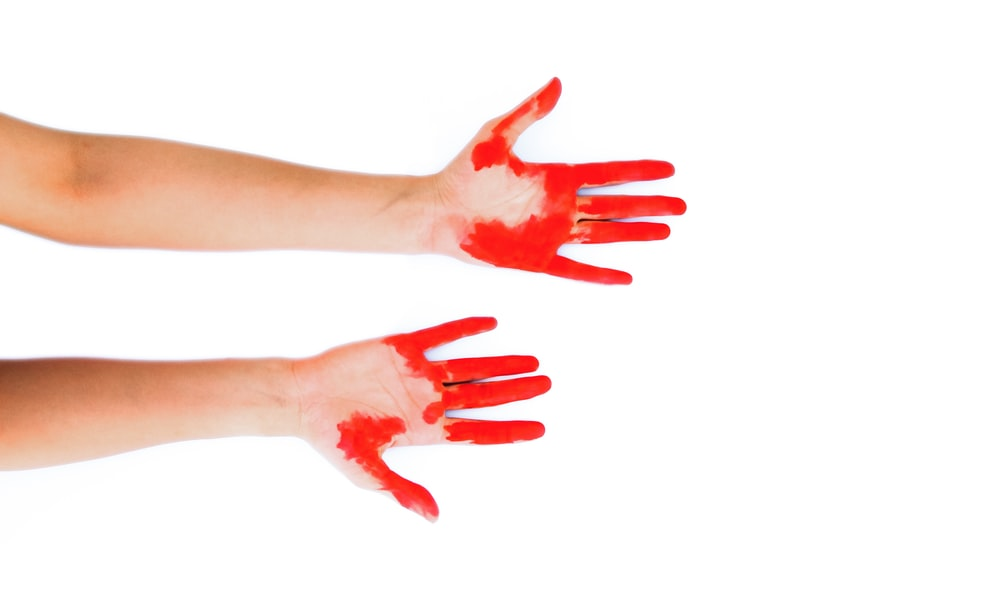 persons hand with red stain