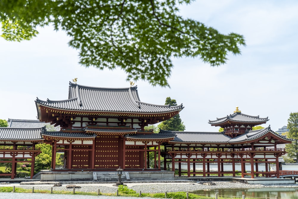 red and white temple near green trees during daytime