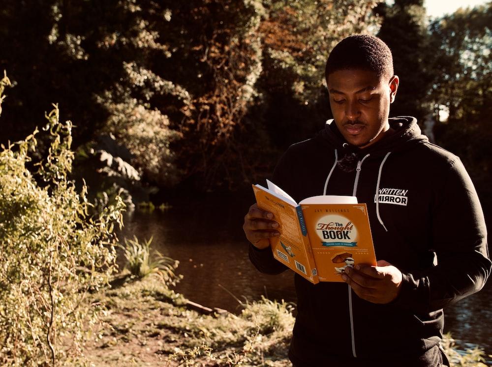 man in black jacket holding book near lake during daytime