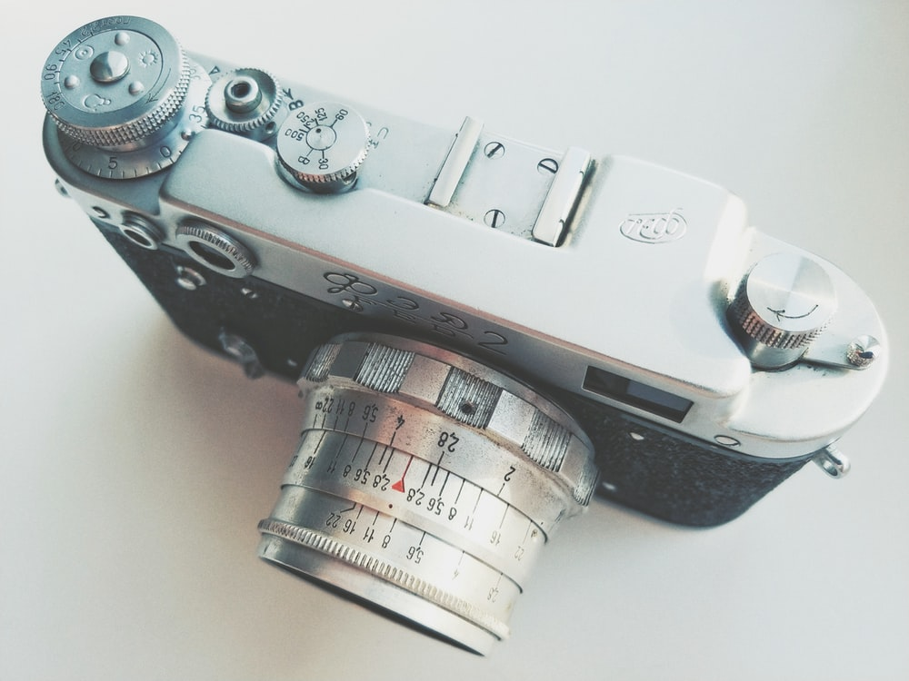 silver and black camera on white table
