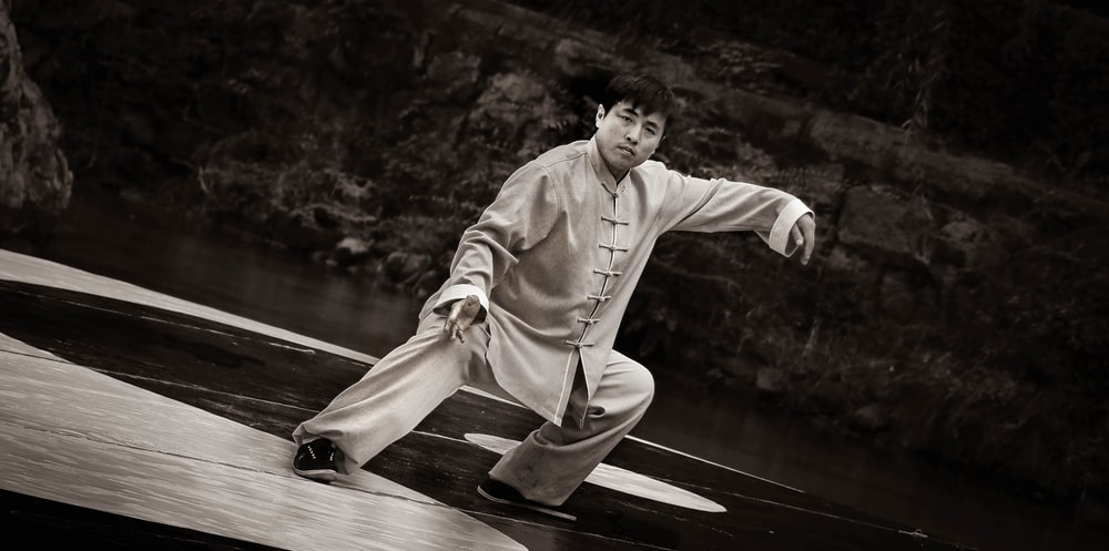 man in white robe sitting on wooden dock