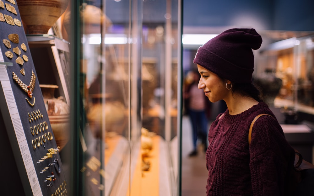 woman in purple knit cap and purple knit sweater looking at glass window