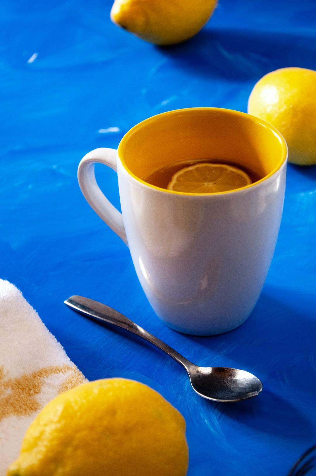 Lemon tea on blue background and spoon / Thé au citron sur fond bleu et petite cuillère