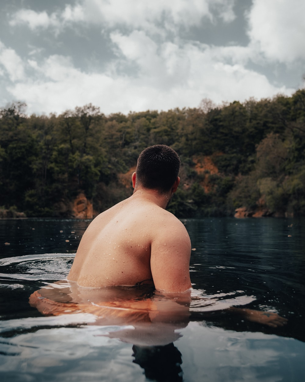 topless man in water near green trees during daytime