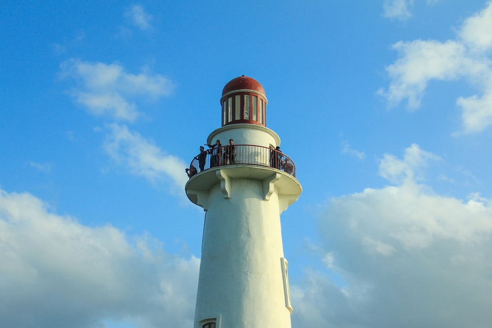 white and red concrete lighthouse under blue sky during daytime