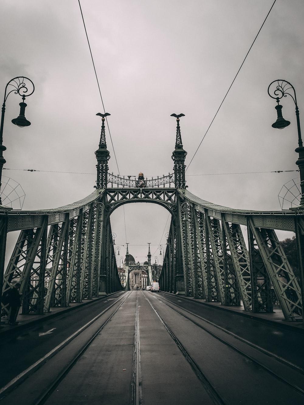 people walking on bridge under cloudy sky during daytime