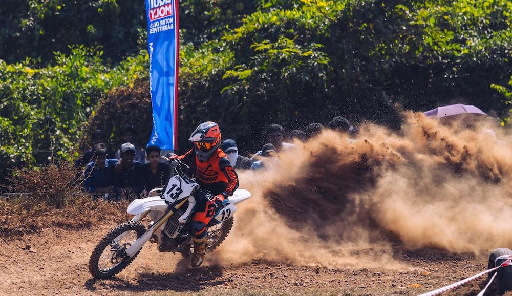 man in red and white motocross helmet riding motocross dirt bike
