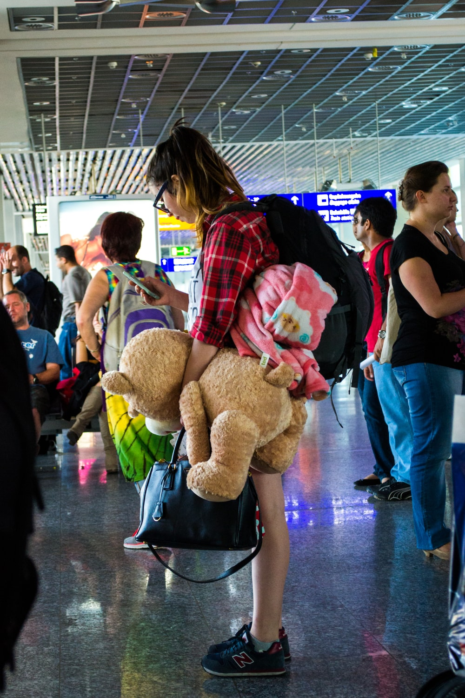 woman in black shirt holding brown bear plush toy