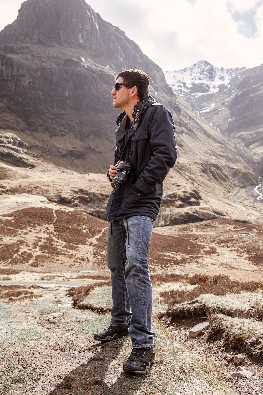 man in black jacket and blue denim jeans holding black dslr camera standing on brown rock