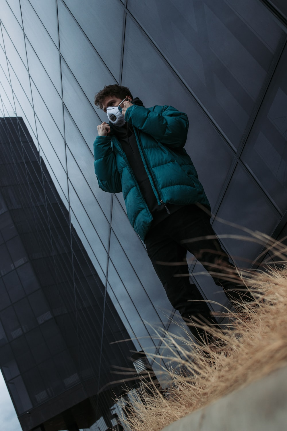 man in green jacket and black pants taking photo of building during daytime