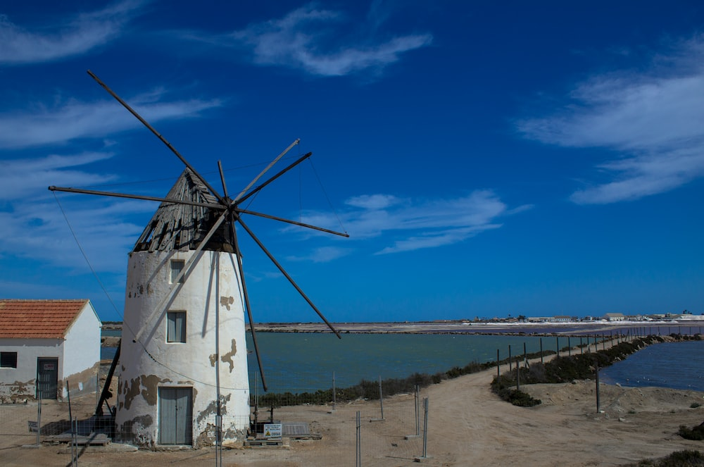 white and brown windmill near sea under blue sky during daytime
