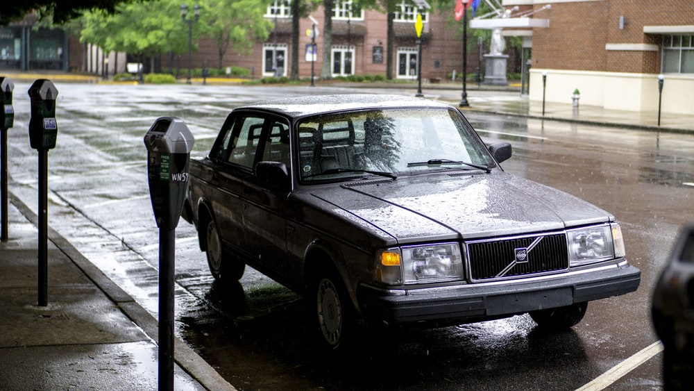 black sedan parked on sidewalk during daytime