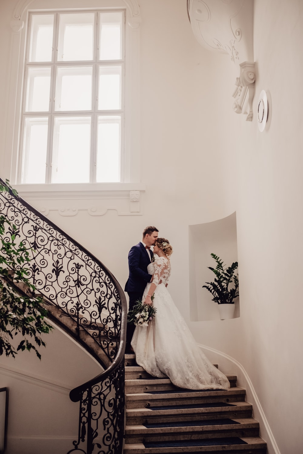 bride and groom standing on stairs