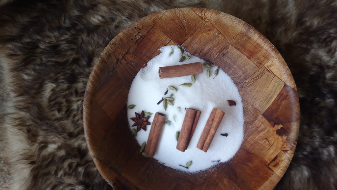 On a fur is placed a wooden bowl containing powdered sugar, cinnamon sticks, star anise, cardamom grains