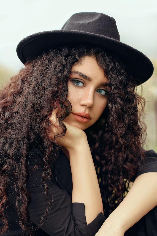 woman in black sleeveless top wearing black hat