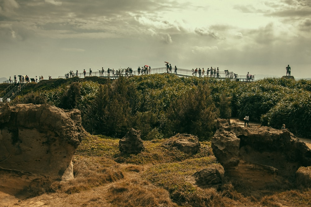 people walking on brown rock formation under white clouds during daytime