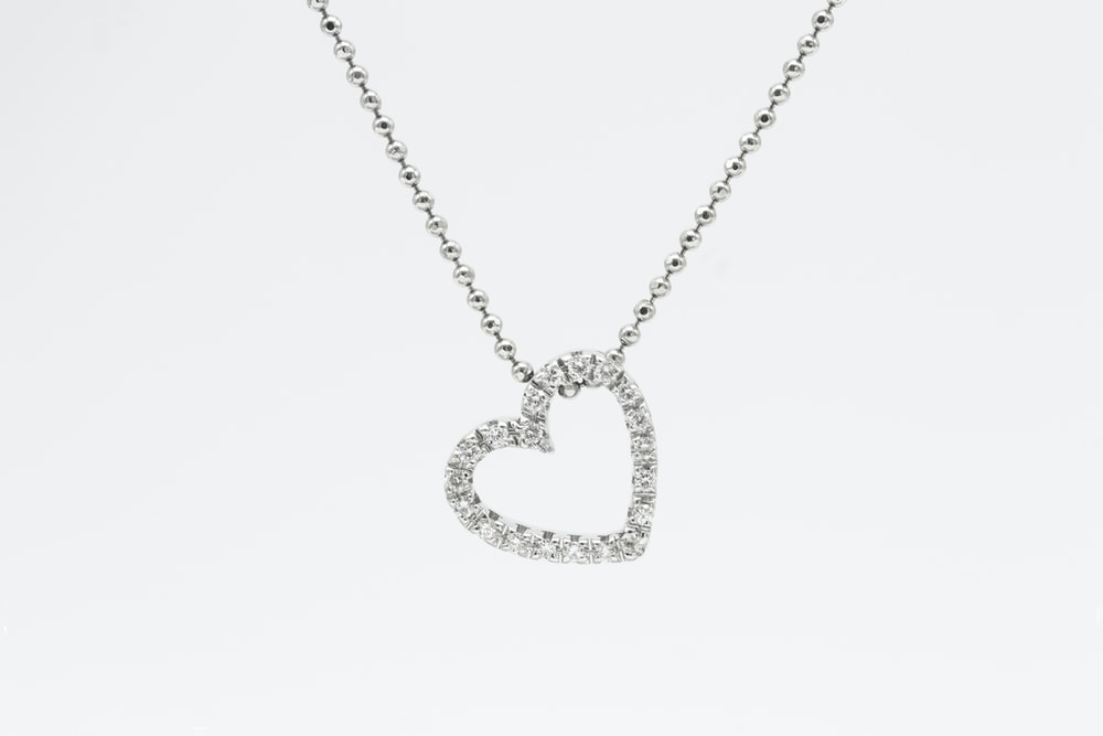 silver heart pendant necklace on white background