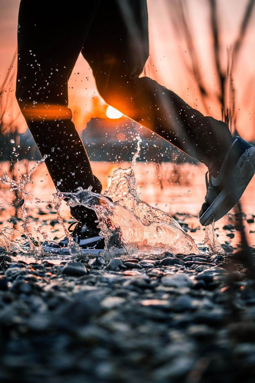 person in black and white nike athletic shoes standing on water