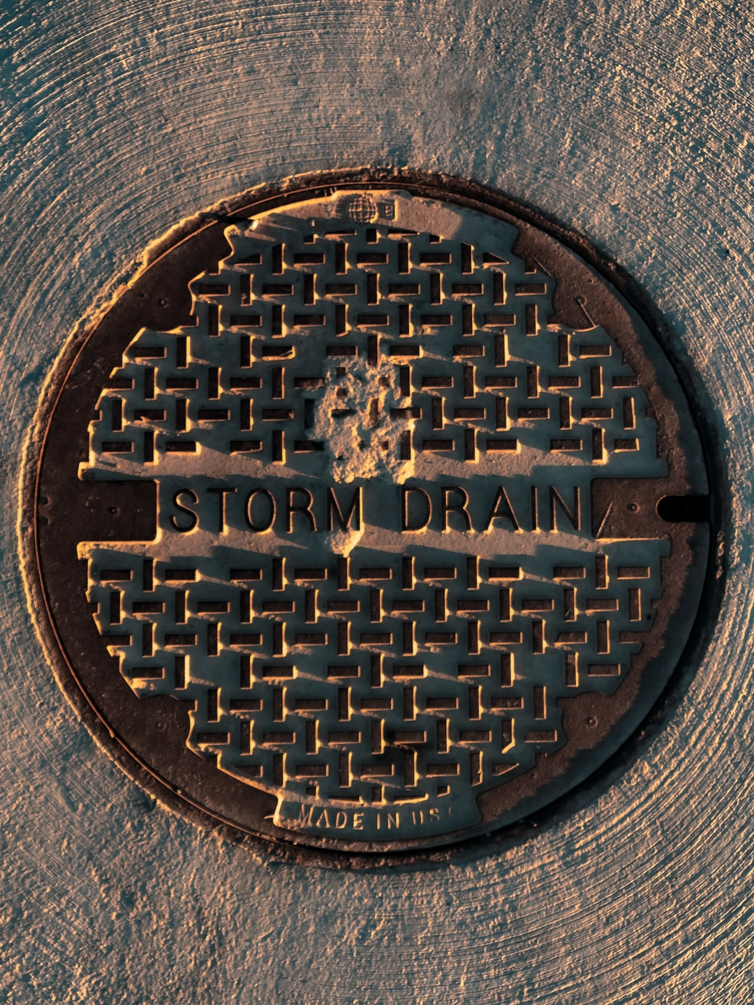 Circlular storm drain lid at golden hour