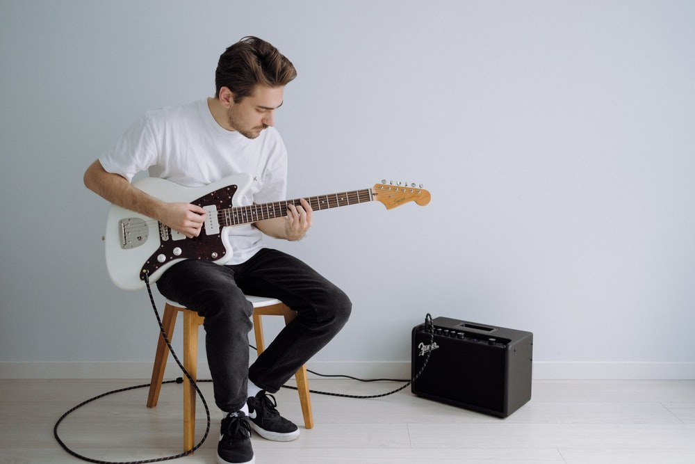 man in white crew neck t-shirt playing electric guitar