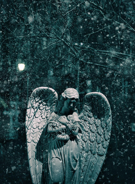 angel statue under white string lights