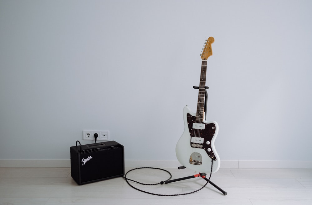 white and brown stratocaster electric guitar on black guitar amplifier