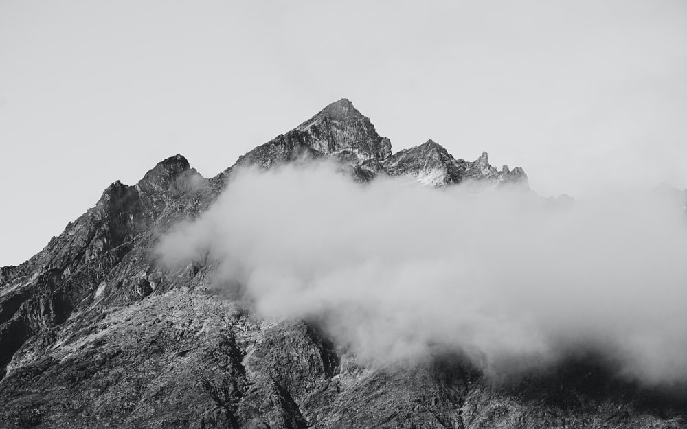 grayscale photo of mountain covered with clouds