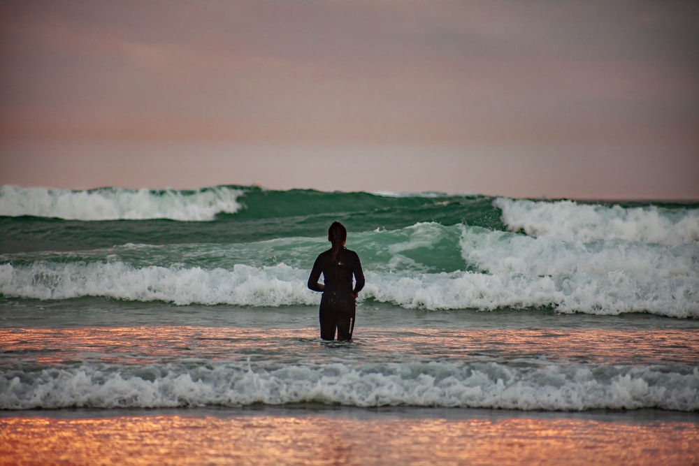 man in black wetsuit standing on sea shore during daytime