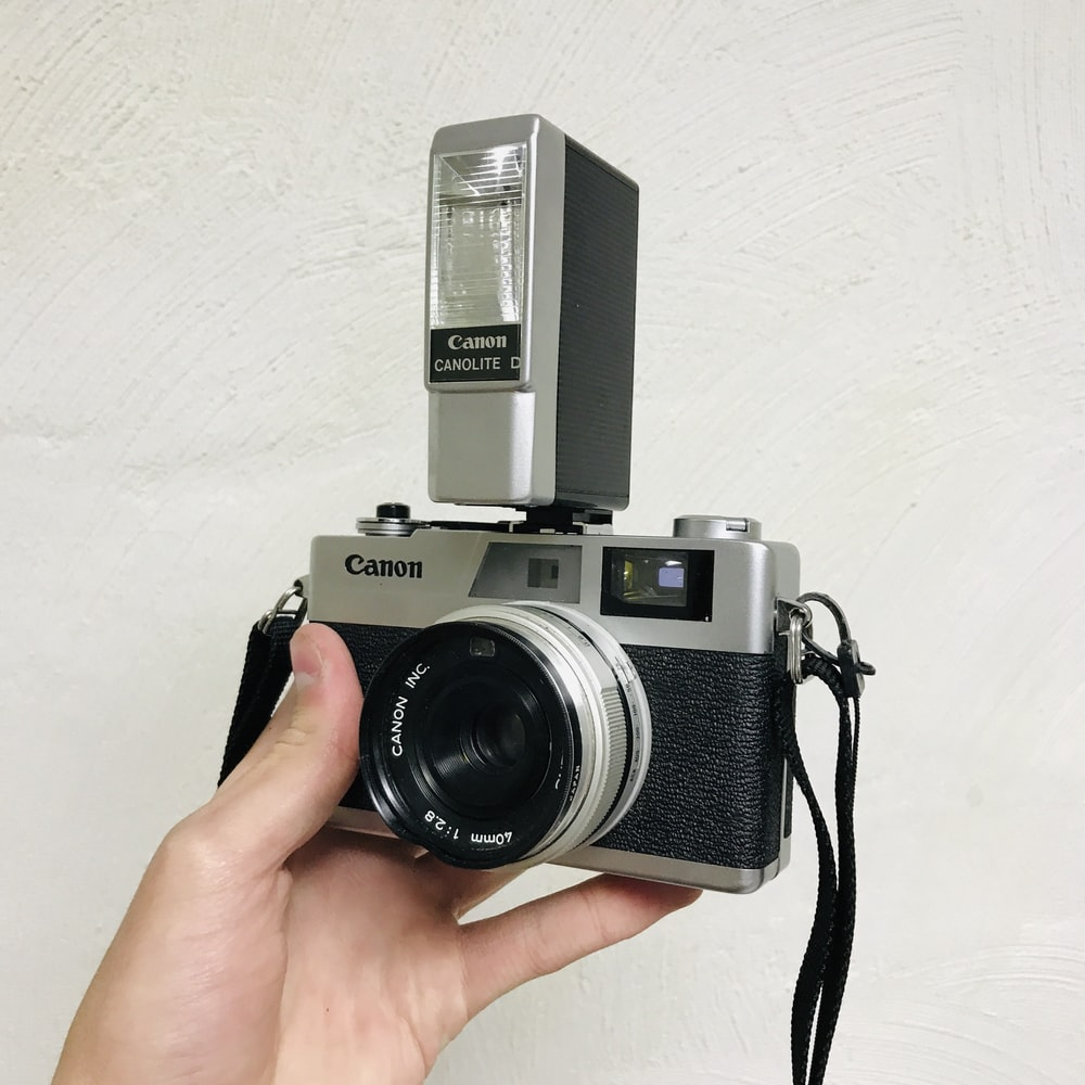 person holding black and silver camera