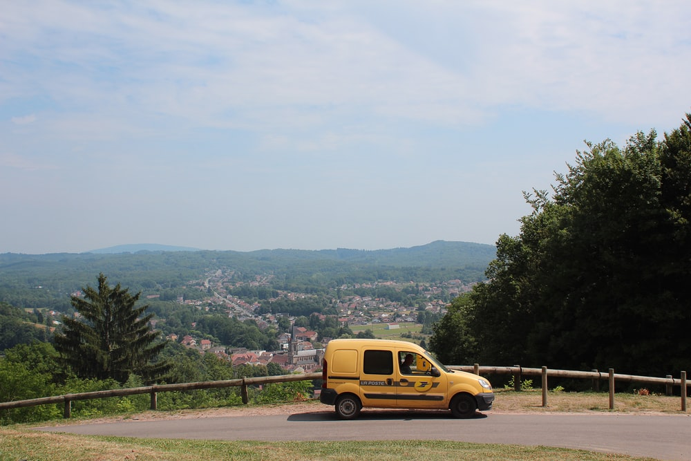 yellow van on road near green trees during daytime