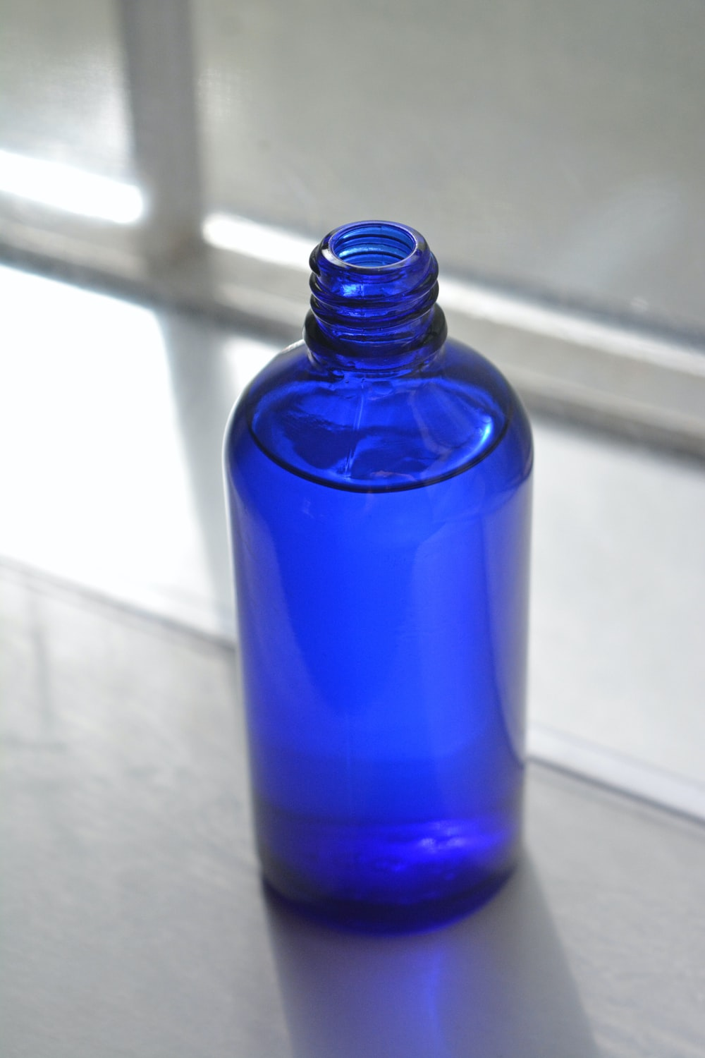 blue glass bottle on white table