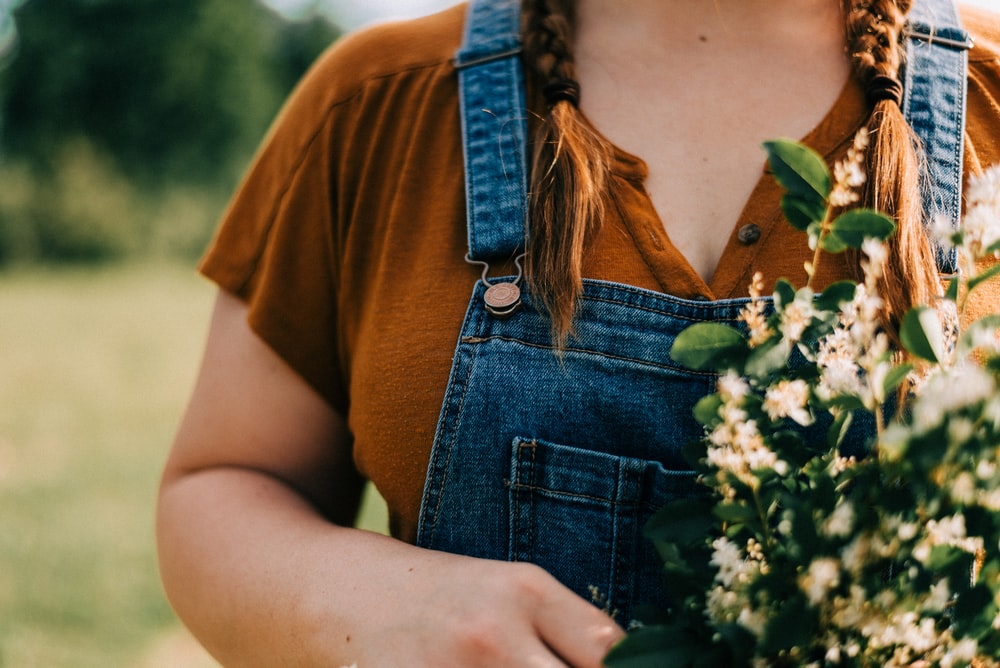 woman in brown crew neck t-shirt and blue denim dungaree holding white flowers