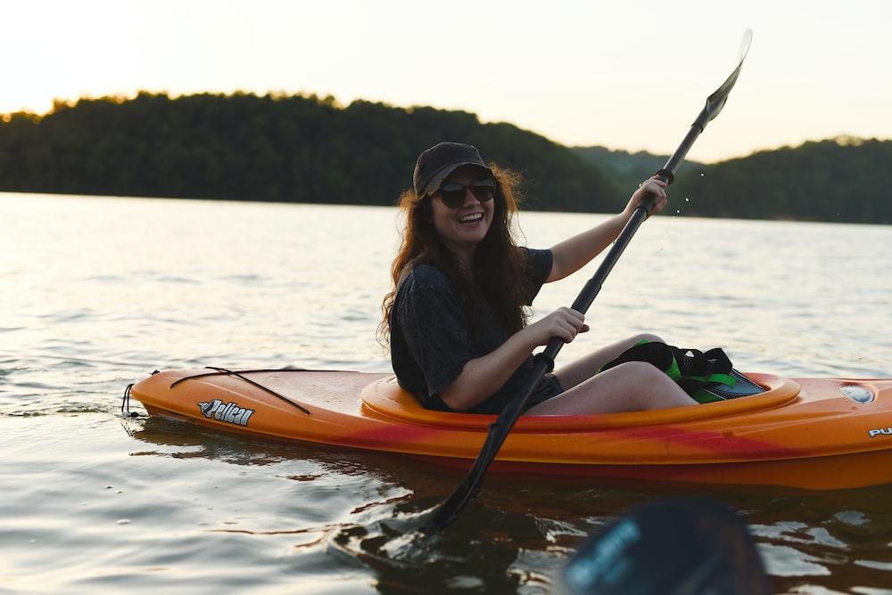 woman in black shirt riding orange kayak on lake during daytime
