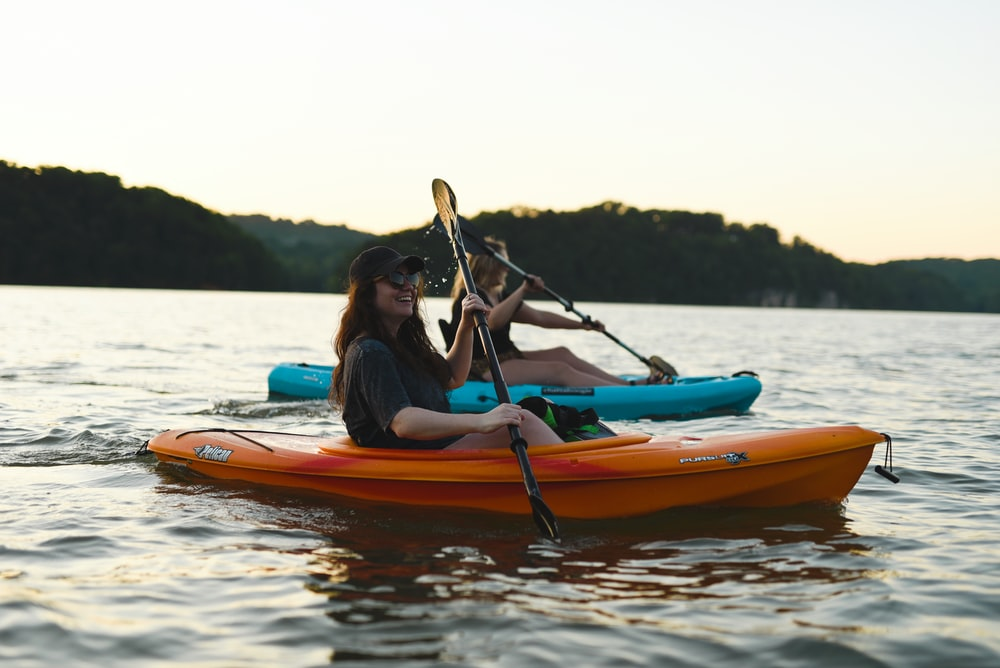 woman in blue shirt and blue denim jeans riding orange kayak on water during daytime